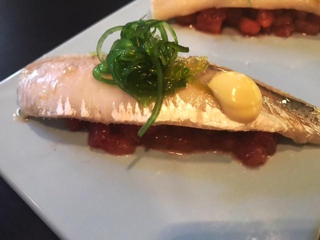 Sardina marinada sobre falso tratar de tomate y fruta
